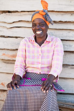 african fabric: An African woman outside of her home