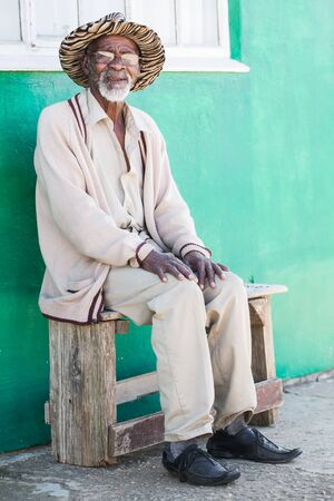A old man is sitting on a bench outside of his home  Stock Photo