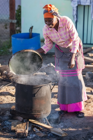 An african woman is making food the traditional way  photo