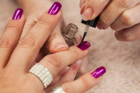 The beautician is painting the second of three layers  Stock Photo