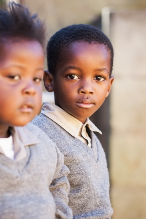 indigence: Two little friends waiting for the taxi to go to school  Stock Photo