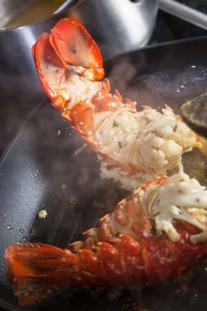 restuarant: TWo parts of crayfish being cooked in the frying pan.