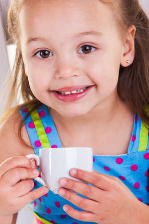 She is drinking her tea from a very small cup. photo