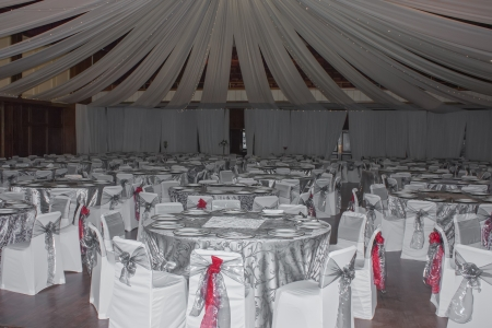 The entire space is draped with white, silver and red. photo