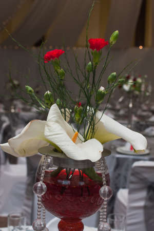 A centre piece on the stage with flowers, glass and red colourance. Stock Photo - 16018834