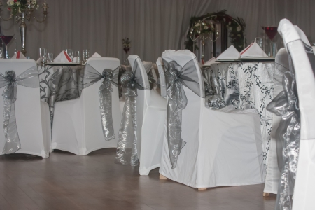 Most of the chairs have only white with a silver draping. photo