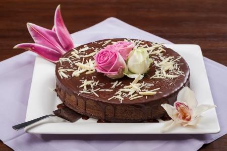 chocolaty: A big chocolate cake with sauce and some flowers.