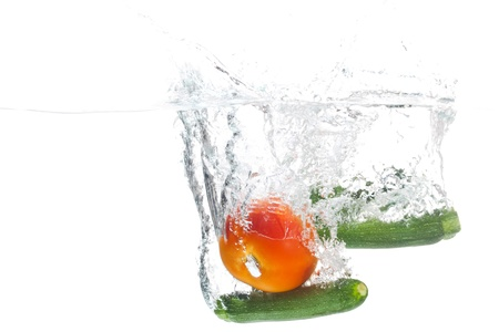 A big tomato and two baby marrows are being cleaned in water. Standard-Bild