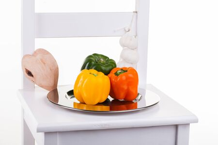 Peppers in a silver plate on a chair with garlic on the side. Stock Photo - 16018900
