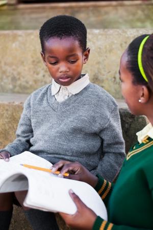 La fille aident son petit frère à faire ses devoirs anglais. Banque d'images - 20359441