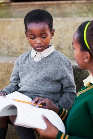 africa child: The girl are helping her little brother with his English homework.