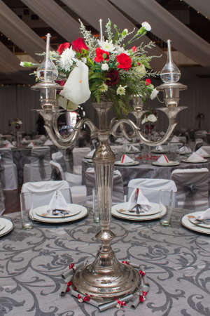 A beautiful center piece on the table with oil lamps and flowers. photo