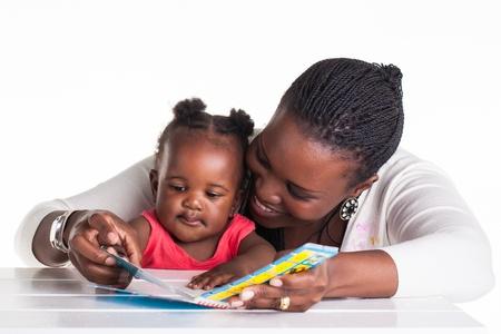 母は彼女の娘に本の中でいくつかの写真を見せています。