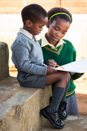 south african: A young lady is helping her little brother with work  Stock Photo