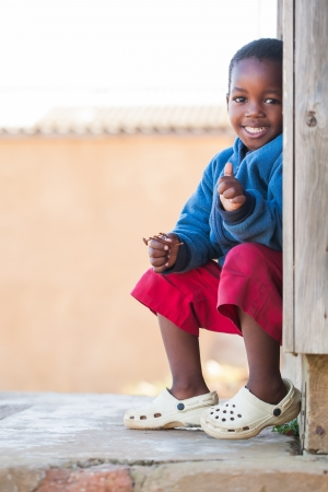 poor african: Little boy outside on the porch of his home. Stock Photo