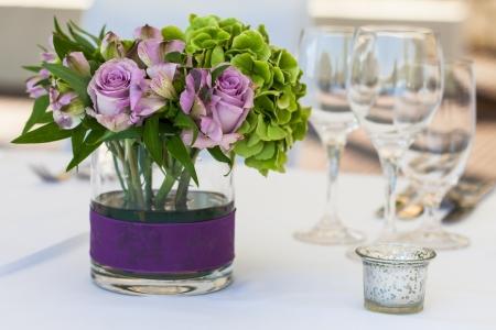 velvet dress: A purple rose center piece on the table.