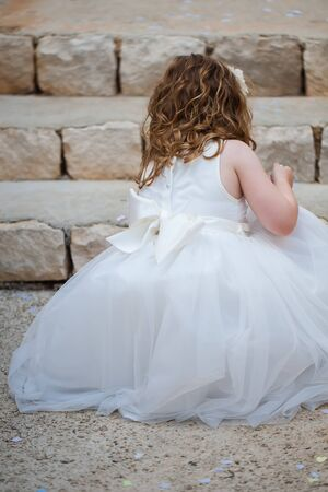 flowergirl: The little girl are picking up the confetti from the ground. Stock Photo