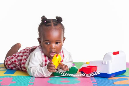 black carpet: A little girl having fun playing with a telephone on her letter carpet.