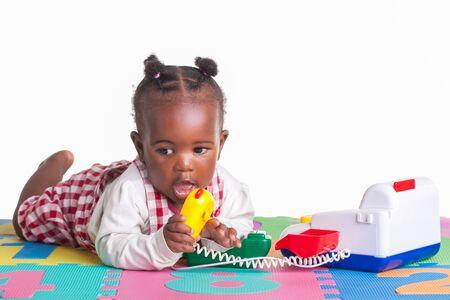 niños negros: Una niña que se divierten jugando con un teléfono en su alfombra carta.