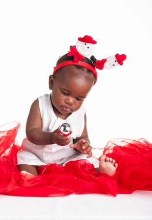 christmas baby: A little African baby dressed for Christmas and some silver decorations.