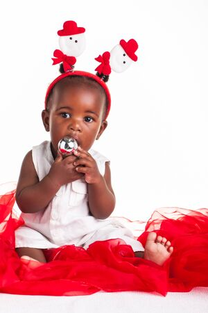 A little African baby dressed for Christmas and some silver decorations. photo