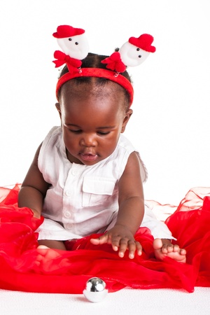 A little African baby dressed for Christmas reaching for a silver ball. photo