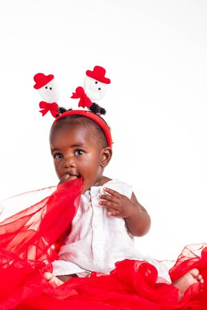 little girl feet: The african baby girl is dressed for the Christmas season and playing with the organza.