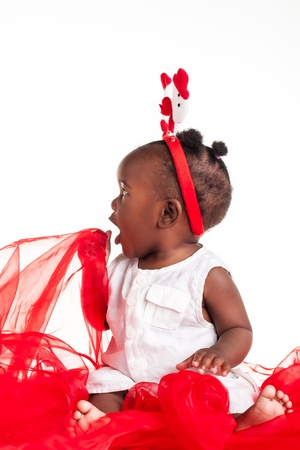 The african baby girl is dressed for the Christmas season and playing with the organza. photo