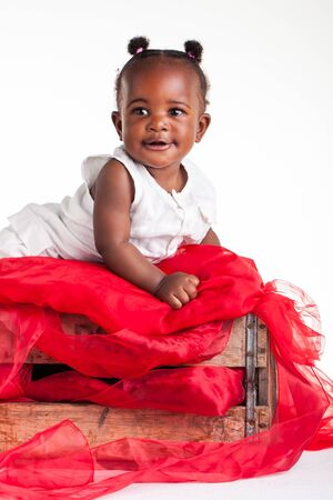A little African baby laying in a wooden crate. photo