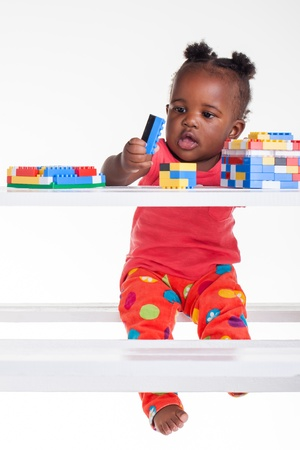 The little baby girl is playing with her blocks on the table.