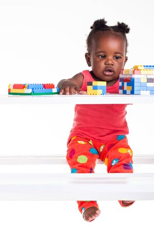 The little baby girl is playing with her blocks on the table. Stock Photo - 17232132