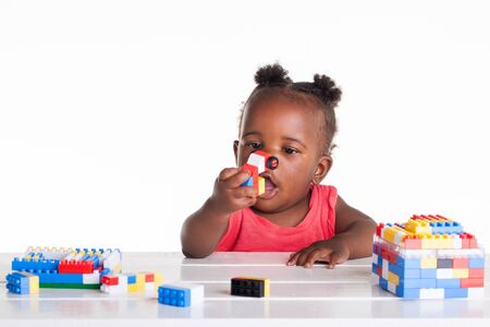 The little baby girl is playing with her blocks on the table. Stock Photo - 17232152