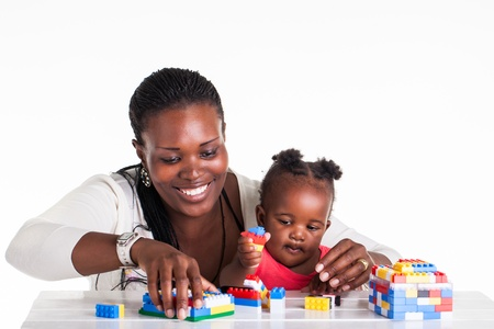family activities: A little baby is playing with building block with her mother. Stock Photo