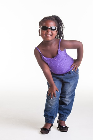 A little African girl dressed in purple blouse, blue jeans and black heels. photo