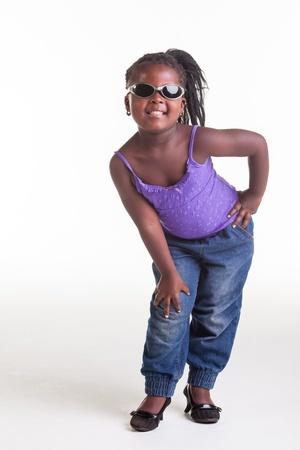 tacones negros: Una ni�a africana vestida con blusa morada, pantalones vaqueros y zapatos de tac�n negro.