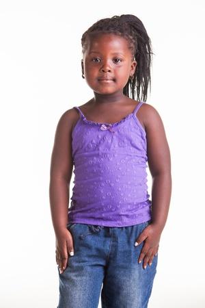 tacones negros: Una ni?a africana vestida con blusa morada, pantalones vaqueros y zapatos de tac?n negro.