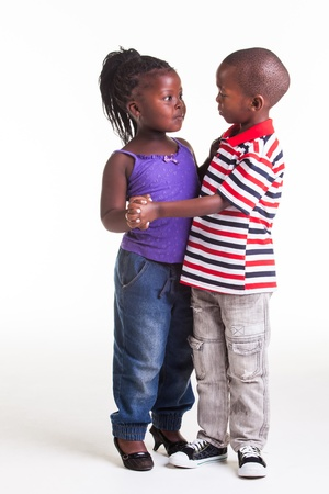 Two young African kids are dancing with each other  photo