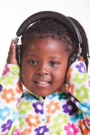 A little girl is listening to music through her earphones  photo