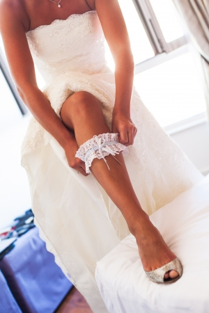 get dressed: The bride are putting on her garter with blue and white lace.