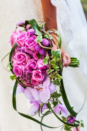 The bride in her wedding dress with her beautiful bouquet filled with pink roses and orchads.