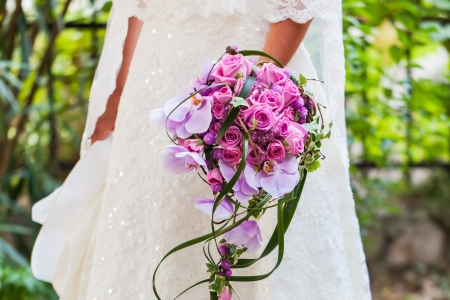 The bride in her wedding dress with her beautiful bouquet filled with pink roses and orchads. photo