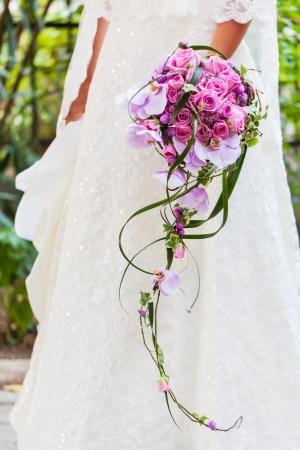 핑크 장미와 orchads 가득 그녀의 아름다운 부케와 그녀의 웨딩 드레스의 신부. 스톡 콘텐츠