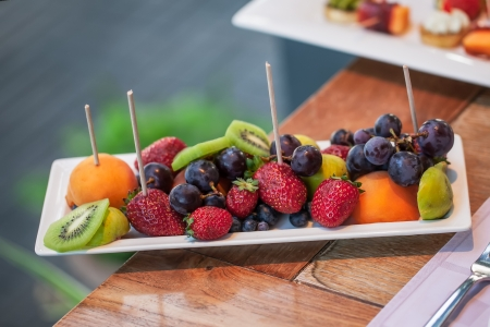 restuarant: Plate filled with peaches, kiwi, red grapes and strawberries.