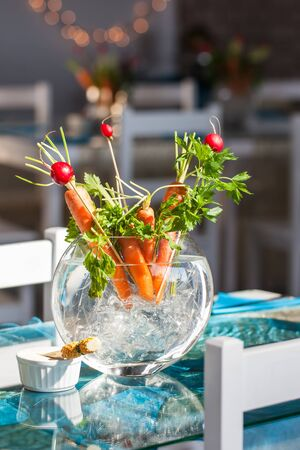 obtained: Carrot and berries ikebana decorations in a glass vase  Stock Photo