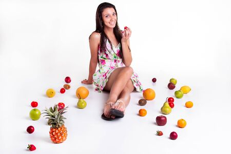 A young model in the studio on the floor with different fruits  photo