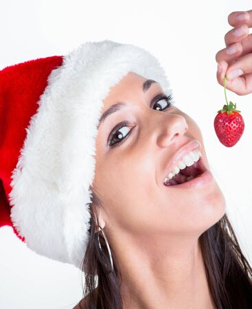 A young female model with a red christmas hoodie and strawberry in the hand Stock Photo - 17234886