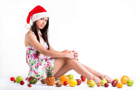 A young teenage model laying on a green organza surrounded with fruit Stock Photo - 17231931