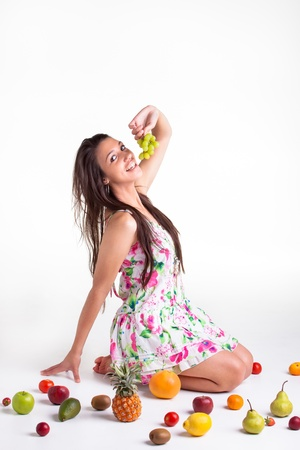 A young model in the studio on the floor with different fruits Stock Photo - 17231930