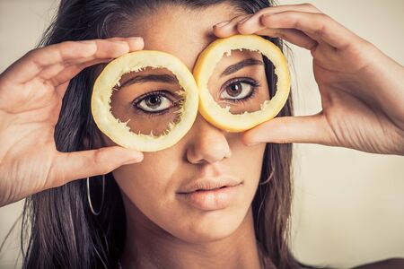 A female model look through lemon skins with a serious face photo