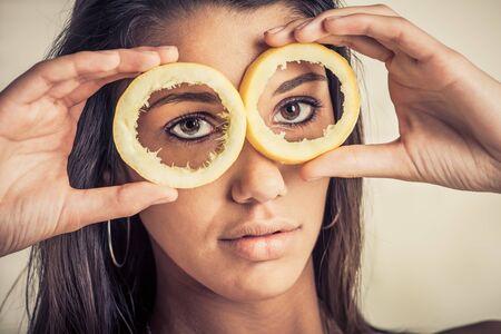 A female model look through lemon skins with a seus face Stock Photo - 17231966